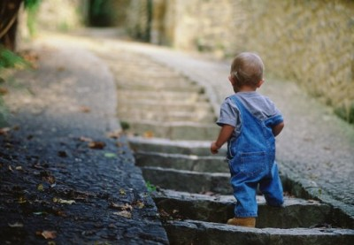 Boy (14-16 months) climbing stone stairway, rear view